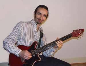 Nat Yelverton Smiling Whilst Playing Guitar