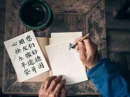 Възрастен китаец пише йероглифи