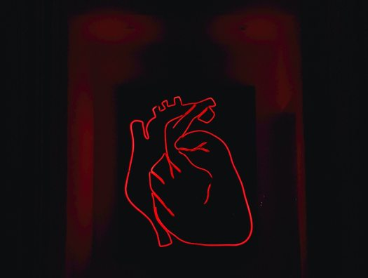A red neon sign depicting an anatomical heart appears against a dark background. What embodied mindfulness means for love is that we must learn to actually feel our feelings in our bodies.