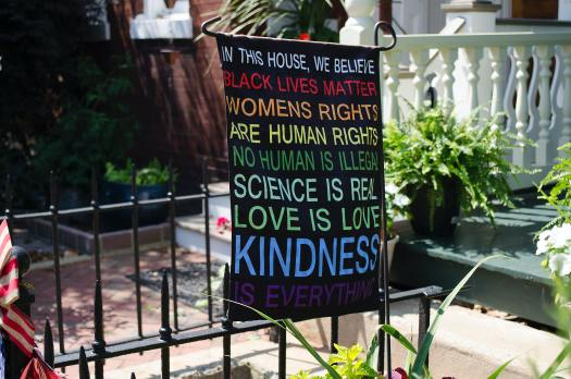 """A banner is hanging in the front yard of the house of someone who cares about social justice, and it reads, """"In this house, we believe black lives matter, women's rights are human rights, no human is illegal, science is real, love is love, kindness is everything."""""""