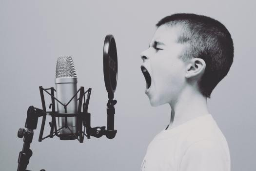 A child with short hair is shouting into a microphone, eyes closed. Calling all dreamers!