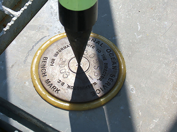 Image shows a benchmark (metal circle engraved with 'National Ocean Service' and 'Bench Mark') - used in tidal gauge set-up