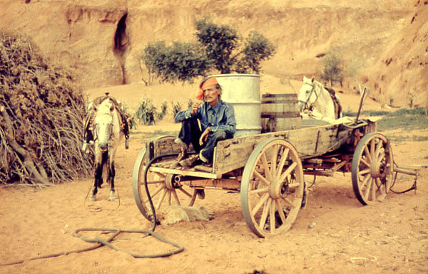 Navajo Man Sitting In Wagon, Two Barrels In The Back Of