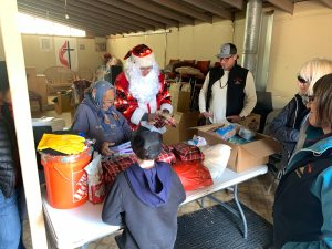 Elder with Santa and volunteers