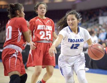 Navajo Times | Donovan Quintero Valley Christian Lady Trojan Anna Gorman (12) drives the ball by guarding Lady Mustangs Jazlyn lane, left, and Ardiana Sheppard (25) Monday in Prescott Valley, Arizona.