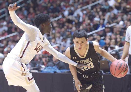 Navajo Times | Donovan Quintero Chinle Wildcat Chance Harvey (20) drives the ball around Winslow's Yoann Djassa on Friday during the Arizona 3A boys semifinals at the Gila River Arena in Glendale, Ariz.