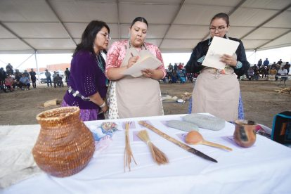 Navajo Times | Ravonelle Yazzie Miss Navajo Nation contestants Autumn Montoya and Summer Jake write down the names of traditional cooking utensils displayed on a table during the traditional food competition of the pageant on Sept. 5.