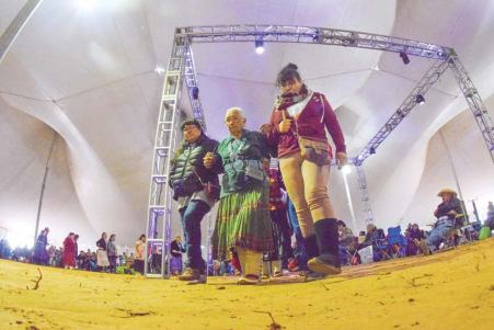 Navajo Times | Krista Allen Arm-in-arm with two women, an older woman dances in a round of skip dance during Elder Fest at the 50th annual Western Navajo Fair on Oct. 11.