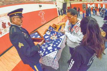 Navajo Times | Krista Allen A woman writes the name of her deceased loved one on a piece of paper while retired U.S. Army Sgt. Paulson Bronston holds an encased burial flag that was unfolded and refolded during a Veterans Day ceremony at Monument Valley High in Tódinéeshzhee' on Nov. 12.