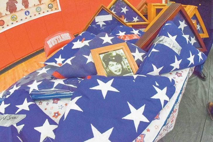 Navajo Times | Krista Allen A portrait of a man in military uniform lies against a burial flag among other Stars and Stripes during a Veterans Day ceremony at Monument Valley High in Tódinéeshzhee' on Nov. 12. Each of the flags were unfolded, refolded, and then presented back to families.