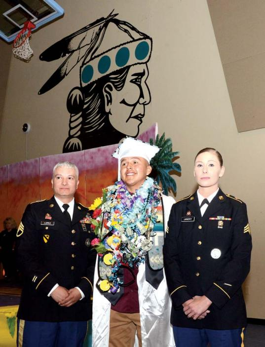 Navajo Times | Paul Natonabah Scholarship recipient senior Douglas Whitehorse poses with Sgt. Jon Lopez, left, and Sgt. Catherine Landry of the New Mexico National Guard who awarded the scholarship to him during Tse Yi Gai High's graduation on Saturday, May 18.