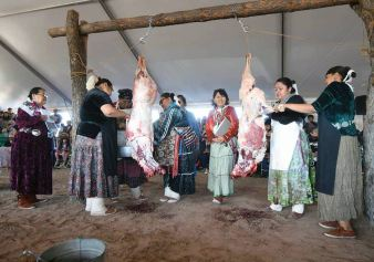 Navajo Times   Ravonelle Yazzie Former Misses Navajo hold the sheep for the two Miss Navajo contestants during the butchering competition on Monday in Window Rock.