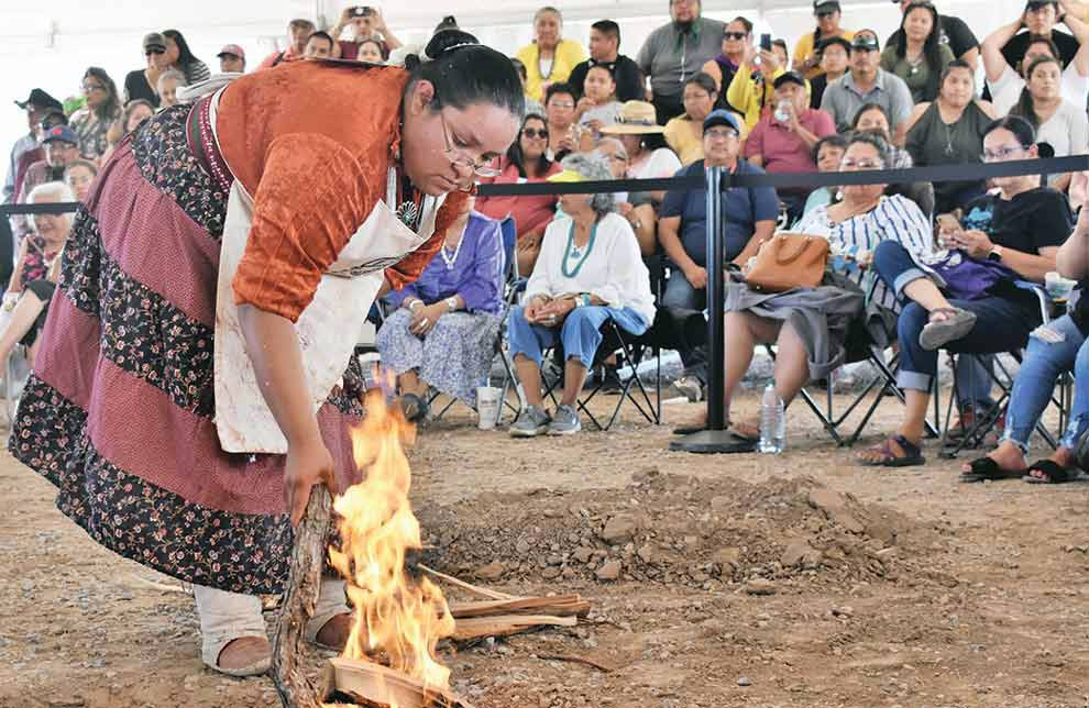 NAVAJO TIMES | RIMA KRISST Miss Navajo Nation contestant Kayla Martinez stokes her cooking fire at the traditional foods competition.
