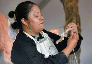 Navajo Times | Ravonelle Yazzie Miss Navajo Nation contestant Shaandiin Parrish shows the audience the ach'íí' she prepared at the butchering competition on Monday in Window Rock.