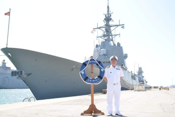 the incoming commander of snmg2, captain manuel aguirre of the spanish navy, poses by the flagship frigate alvaro de bazan.
