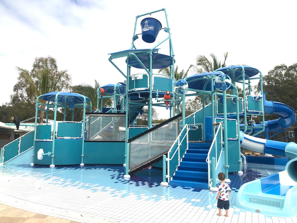 Boy standing in front of Sandstone Point Holiday Park waterpark stairs and bucket