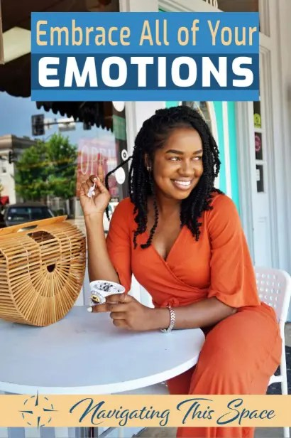 African woman pulls her braided hair with a big smile on her face while embracing her emotions