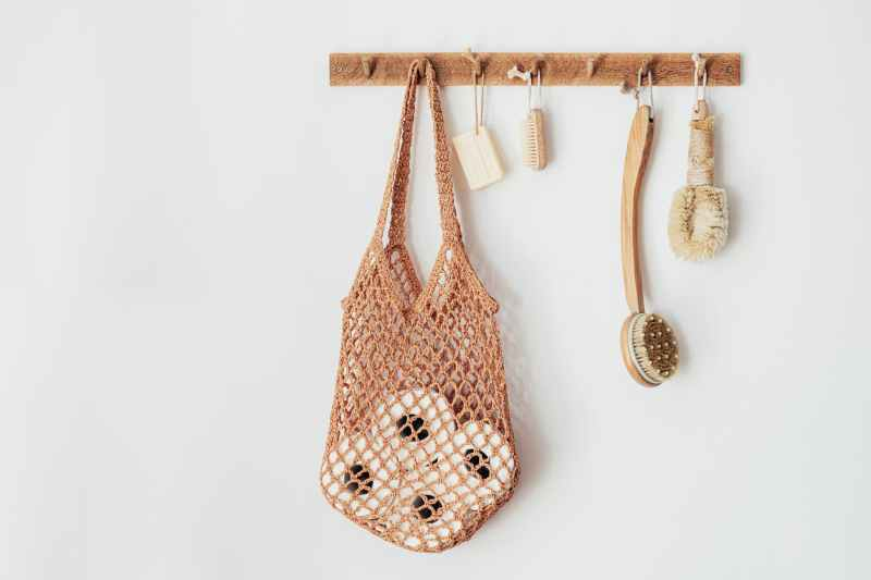 wooden hanger with body brushes and toiletries on white wall