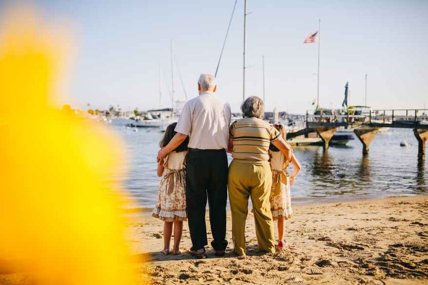 grandparents with their granddaughters standing by the shore