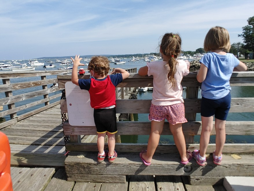 2 girls and boy looking out at a harbor