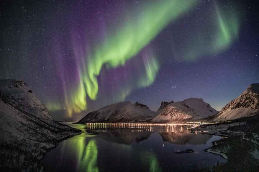 mountain beside body of water with aurora borealis