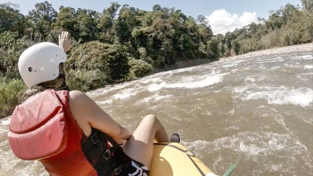 Young woman Whitewater Rafting a Class III rapid on the Balsa River in Costa Rica