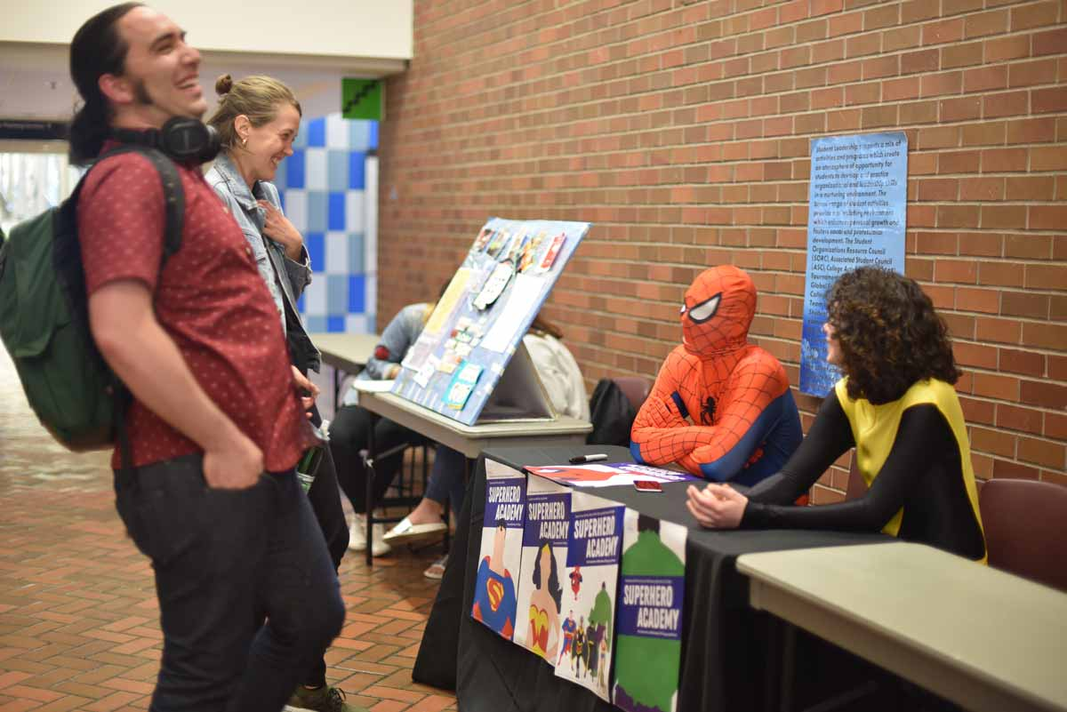 Superheroes setup a table during the college fair