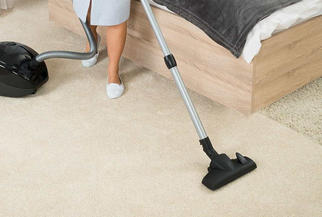 Maid Vacuums Hotel Room
