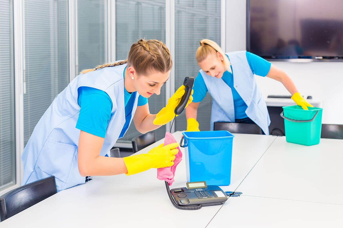 Cleaning Workers Wipe Down Surfaces in Business Office
