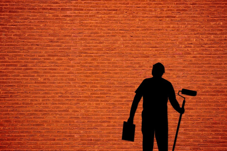 A red brick wall with a silhouette of a man with a paint roller.