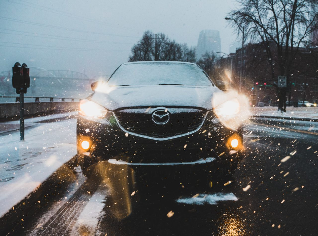 A parked car shines its headlights during a snowstorm.