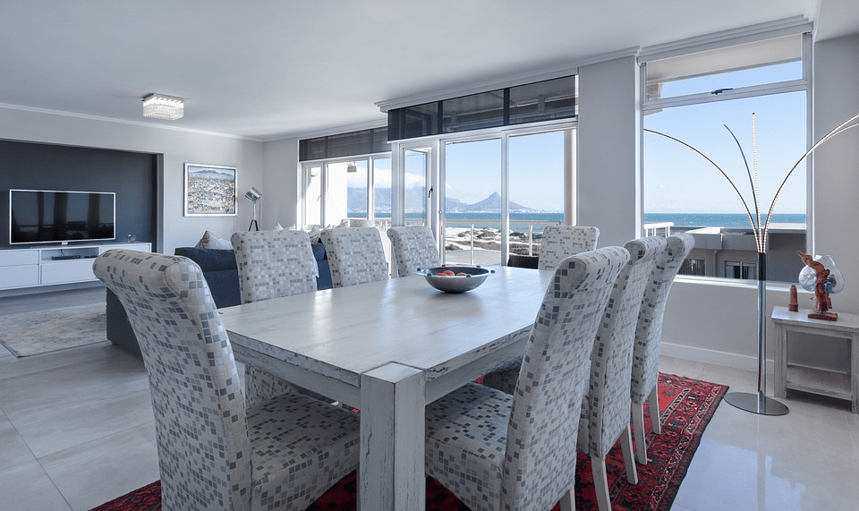 A modern dining room with big bright windows