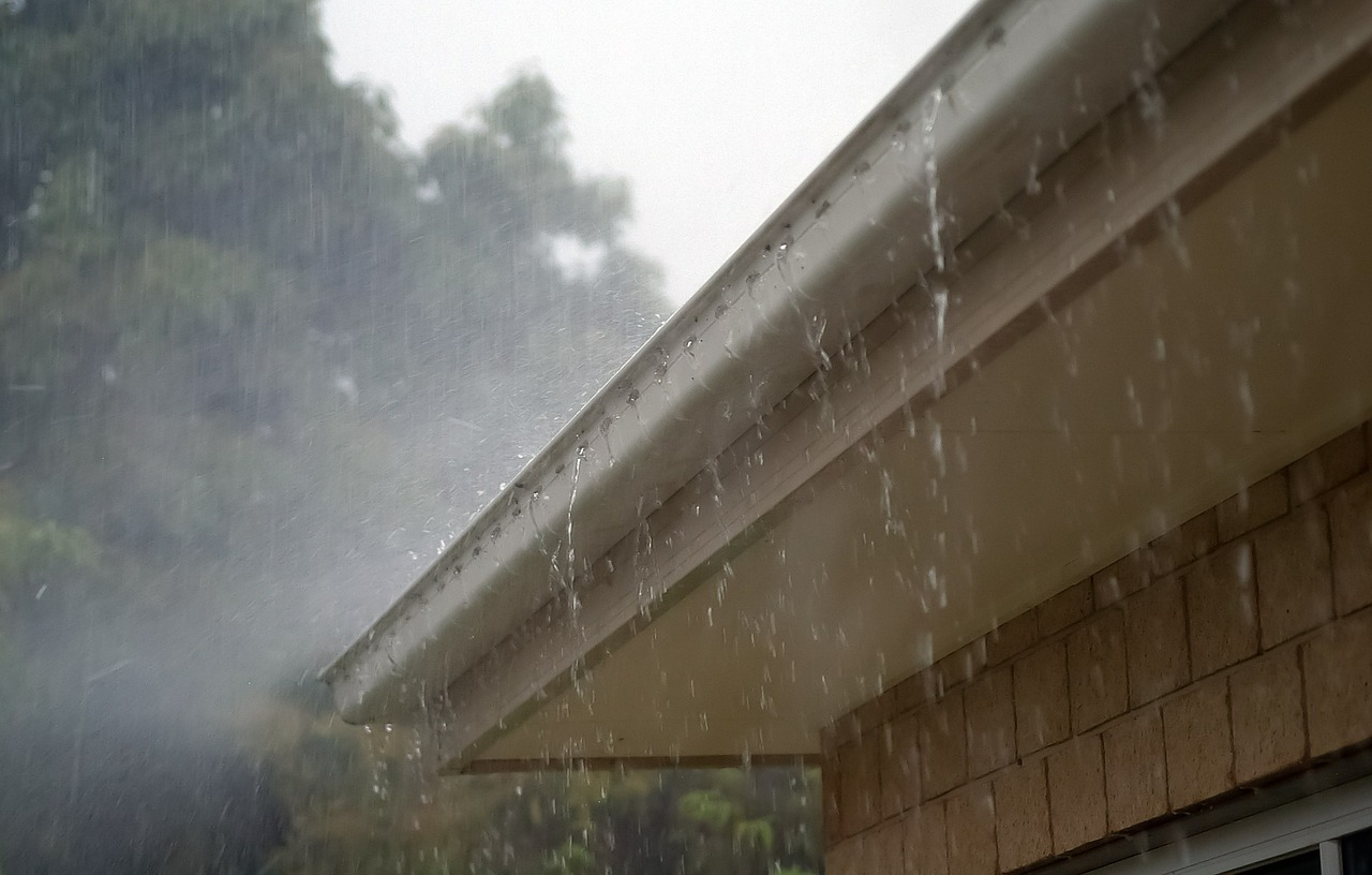 A home without rain gutter guards is caught in a downpour of rain.