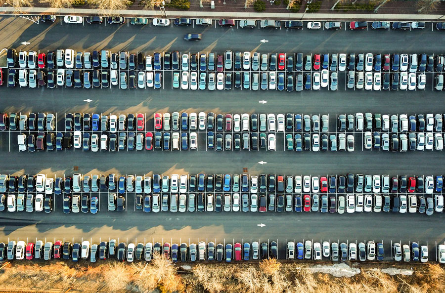 Cars parked neatly in a large parking lot.