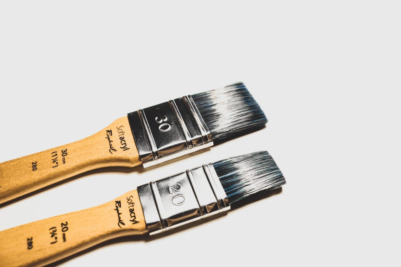 Two brown paint brushes used in deck maintenance tasks