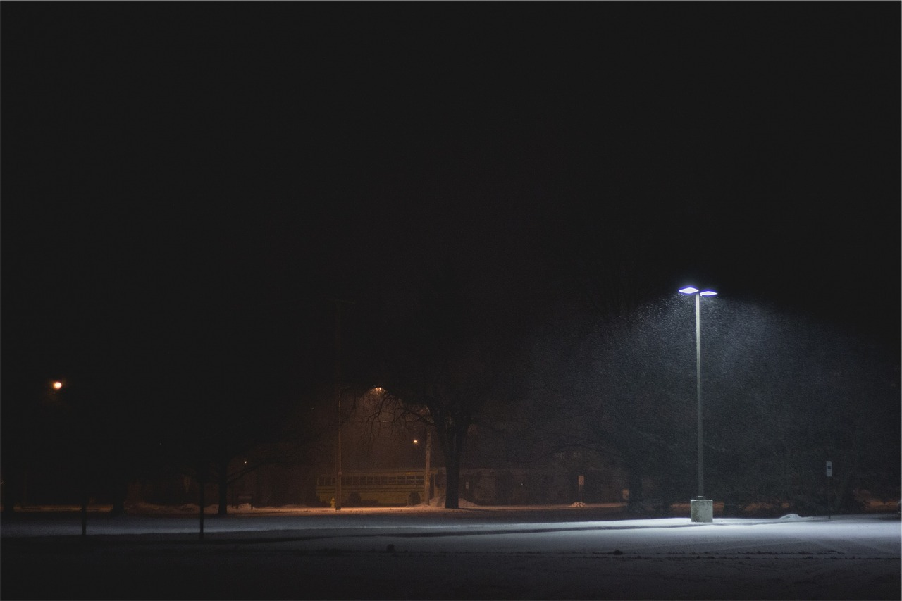 A snowy parking lot on a winter night, with one area well-lit and the other area dark.