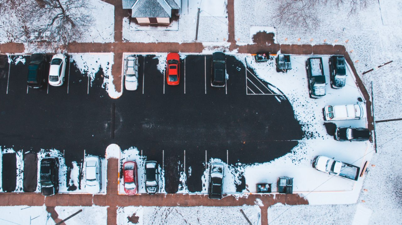 A snowy parking lot seen from above.