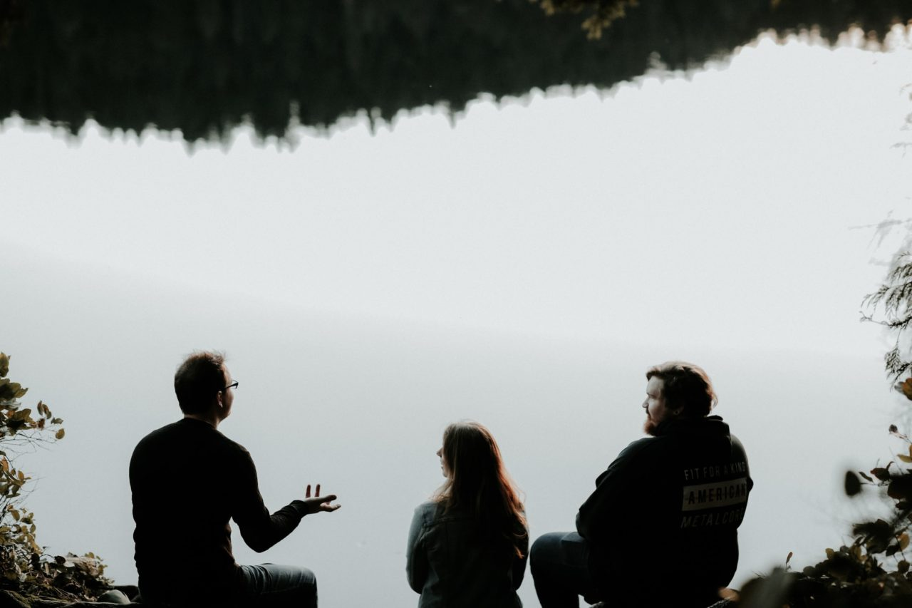 A group of neighbors talk about wildfire home protection while sitting near a lake.
