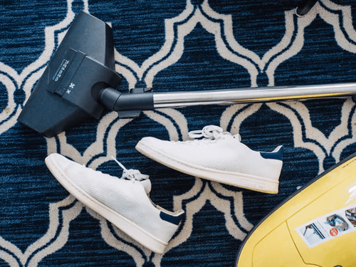 White shoes sit next to vacuum cleaner on blue rug