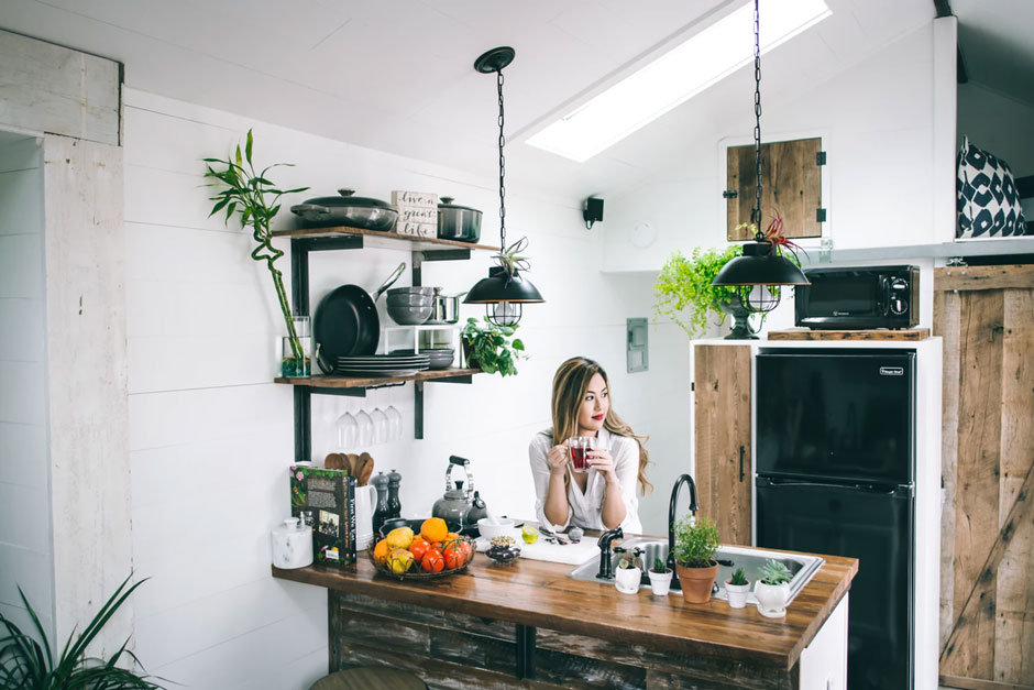 Woman sips tea at the counter in her rustic kitchen.
