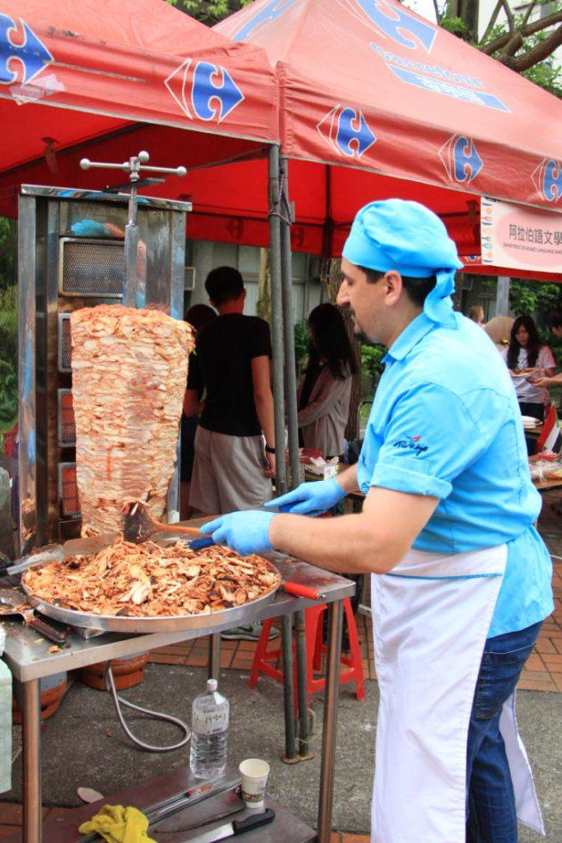 「土耳其」攤位的特色商品為烤雞肉捲餅,在攤位旁邊將烤雞肉放置於機器上面現切現賣,有趣畫面吸引許多客群。(黃堃睿攝)