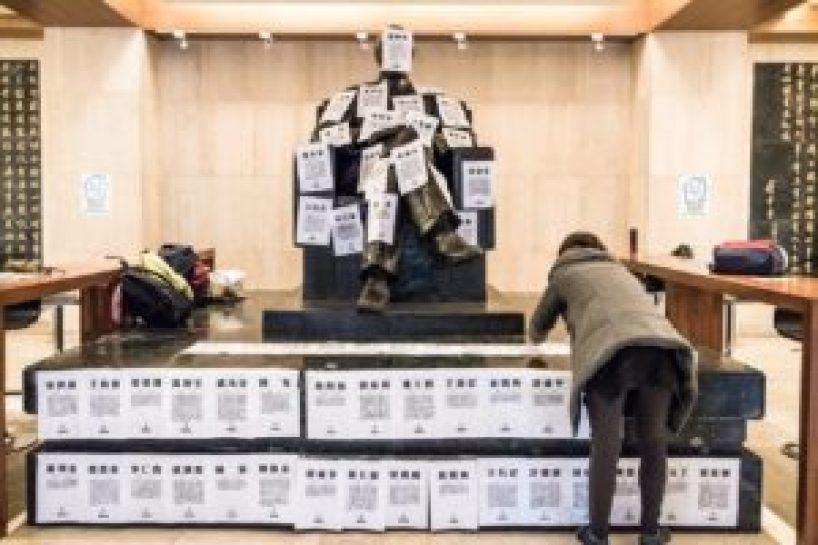 政大野火陣線於蔣中正銅像基座上黏貼二二八事件受難者名單。(圖/孫晨哲攝)