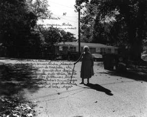 A grandmother standing outside with overlayed, indistinguishable text