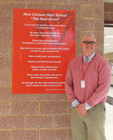 "Mr. Egan smiles next to one of the larger ""New Norms"" posters by the spiral staircase. Photo by Sofia Paloka."