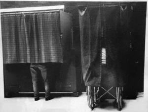 A black and white photo of two voting booths with curtains. Behind one curtain is a person in a wheelchair and behind the other voting booth curtain is someone standing.