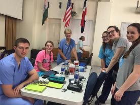 Pharmacy and PA students chat with Deb, a nurse practitioner, as they prep the triage area of the clinic.