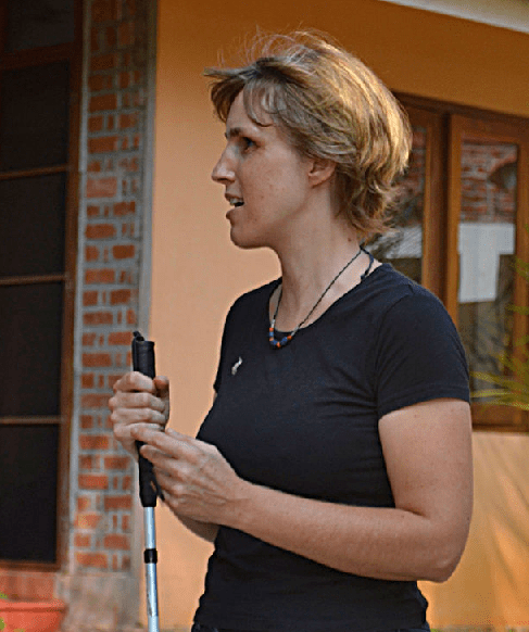 A blind woman in a black shirt standing outside a brick building and holding her white cane upright in front of her.