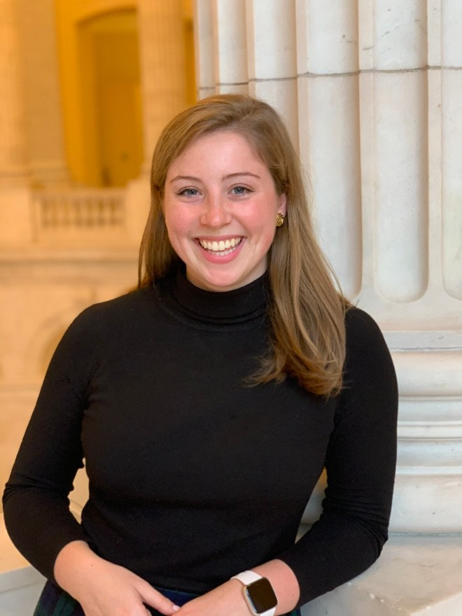 Sara is wearing a dark, form-fitting turtleneck and a smartwatch. She has brown hair slightly past her shoulders. She is smiling at the camera and in the background is the Supreme Court building.