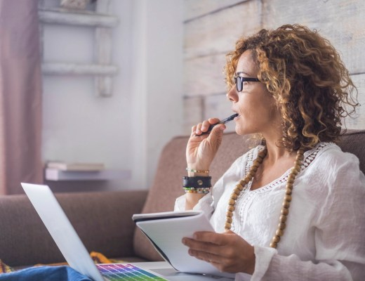 Woman thinking with laptop and notes