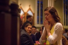 A student prays before the start of the Paschal Vigil Mass on Saturday.